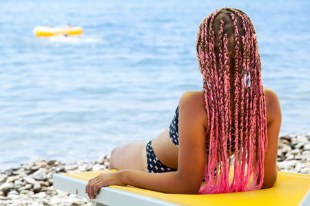 Photo pour Rear view of pretty girl with pink African braids lying back on yellow sun lounger on coastline - image libre de droit