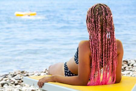 Foto de Rear view of pretty girl with pink African braids lying back on yellow sun lounger on coastline - Imagen libre de derechos