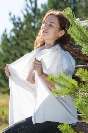 Photo for Pretty woman with unbuttoned shirt and naked breasts in sunny meadow in forest - Royalty Free Image