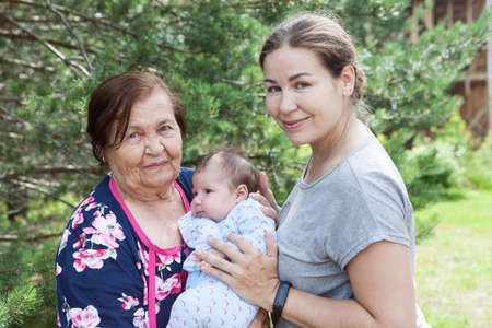 Photo pour Great grandmother with her granddaughter and great-granddaughter, three people portrait at summer season - image libre de droit