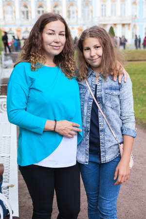 Photo for Pretty mother and daughter portrait in the park, looking at camera and smiling, curly long hairs - Royalty Free Image