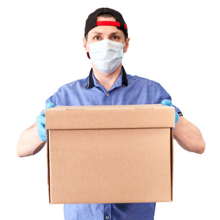 Photo for Caucasian delivery man wearing medical mask and blue surgical gloves brings cardboard, isolated on white background - Royalty Free Image