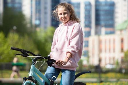 Photo pour Blond Caucasian teenage girl sitting on her blue bicycle, portrait outdoor - image libre de droit
