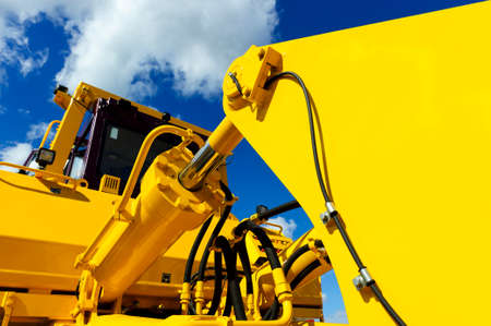 Photo for Bulldozer, huge yellow powerful construction machine with big bucket, focused on hydraulic piston arm, blue sky and white clouds on background - Royalty Free Image