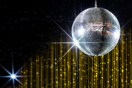 Disco ball with stars in nightclub with striped yellow and black walls lit by spotlight, party and nightlife entertainment industry