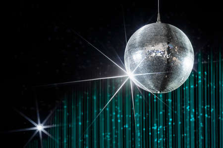 Foto de Disco ball with stars in nightclub with striped turquoise and black walls lit by spotlight, party and nightlife entertainment industry - Imagen libre de derechos