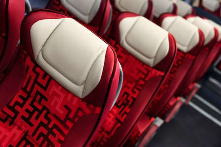 Bus seats in row with red leather, textile coating, wooden armrests, white headrests and mounts for safety belts, modern comfortable tourist transport interior, selective focus