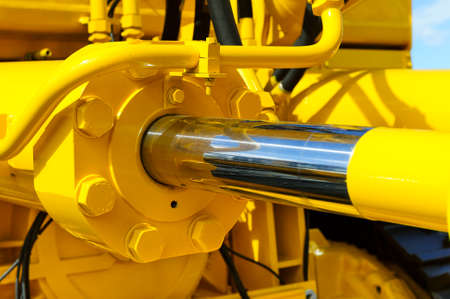 Photo for Hydraulic piston system for bulldozers, tractors, excavators, chrome plated cylinder shaft of yellow machine, construction heavy industry detail, selective focus - Royalty Free Image