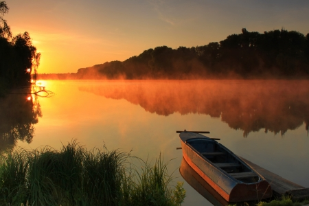 Boat on the shore of a misty lake on a summer morning