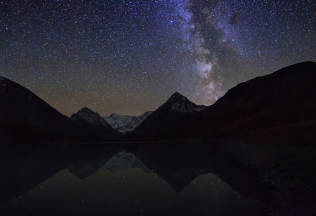 Magic night landscape with mountains frozen lake and amazing starry sky.
