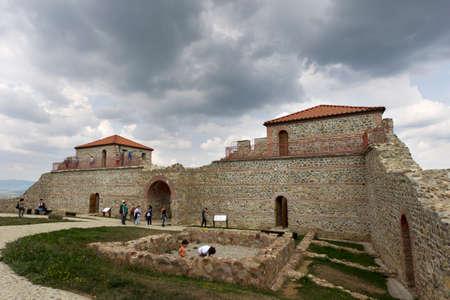 BELCHIN, BULGARIA - SEPTEMBER 3, 2016: Tourists walks arround partly reconstructed roman fortress Cari Mali Grad, near town of Belchin, 3 September, 2016, Bulgaria.