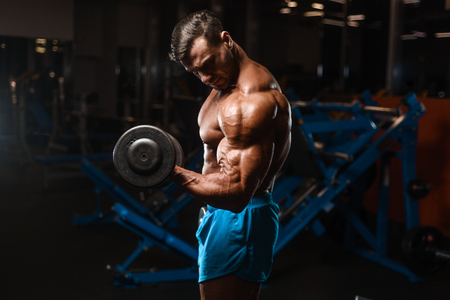 Foto de Handsome young fit muscular caucasian man of model appearance workout training in the gym gaining weight pumping up muscle, poses, drinks water  fitness and bodybuilding sport nutrition concept - Imagen libre de derechos