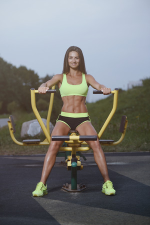 outdoor sport Beautiful strong sexy athletic muscular young caucasian fitness woman workout training in the gym on diet pumping up abs muscles and posing bodybuilding health care and fitness body bar concept