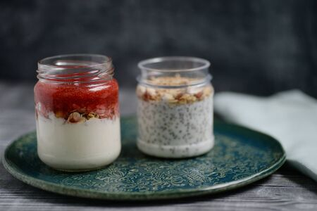 Healthy food, diet and nutrition concept. Early morning breakfast with homemade granola muesli, natural yogurt. Kitchen wooden background Kefir yogurt and chia parfaits powerful probiotics