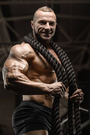 fitness athletes training using battle ropes intense workout team exercise challenge in gym enjoying healthy bodybuilding endurance practice lifestyle together