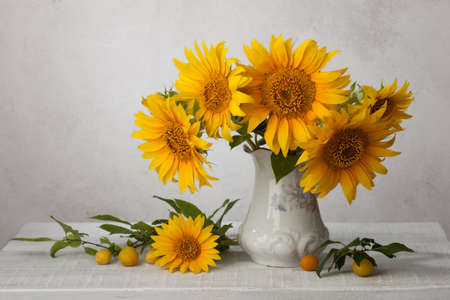 Bouquet  of sunflowers in old ceramic jug   against a white wooden wall.In the foreground branches with ripe cherry plum