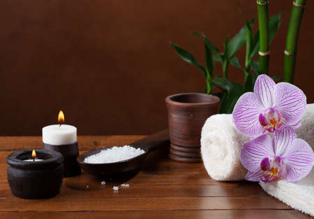Spa setting with sea salt, candles, towels, stones and orchids.