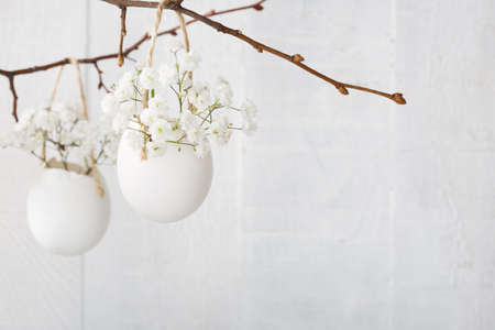 Bunch of white gypsophila  flowers  in eggs shell on the white wooden plank. Shallow depth of field, focus on near flowers. Easter decor