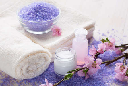 Mineral Bath Salts, towels and moisturizer  in a tranquil spa setting.   Shallow dof. Focus on the  jar of cosmetic cream