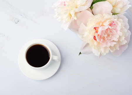Still life with cup of coffee and flowers peonies on light blue wooden table.