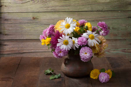 Still life with colourful chrysanthemums bunch on old wooden table