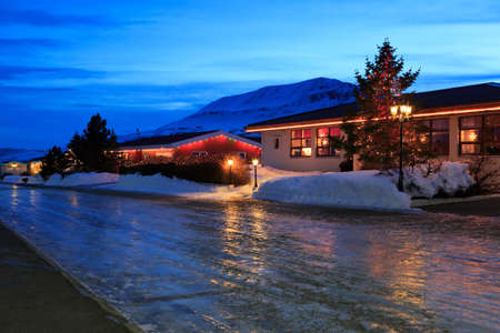 Photo pour Typical Icelandic houses with Christmas decorations at the twilight near Akureyri, Iceland. slippery road in the foreground. - image libre de droit