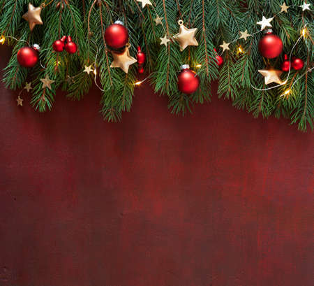 Photo pour Spruce branch with Christmas decorations on the wooden board  painted in dark-red.  Ð¡hristmas  background with empty space for text or image. Flat lay. - image libre de droit