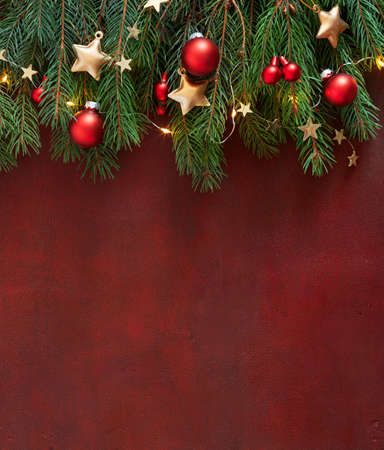 Photo pour Christmas border with fir branches, red baubles and gold stars on the wooden board painted in dark-red with copy space for text. Flat lay. Christmas and New Year holidays background. - image libre de droit