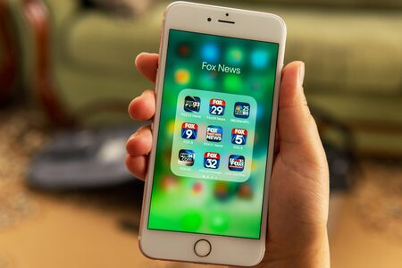 Photo for Palo Alto / USA - August 08 2019: Female hand holding white Apple iPhone with icons of different Fox News media application on the screen. News media icons. Social media or marketing concept - Royalty Free Image
