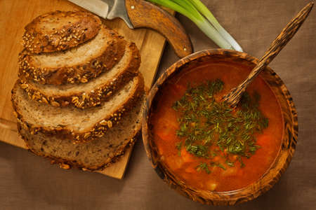 Rural-styled soup served in wooden utensils with wholegrain homemade bread an fresh green onion on the rude tablecloth