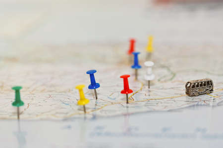 Photo pour Map with road network and with pushpins marking country highlights and tourist attractions and a tiny toy coach on the road. Trip planning via roadmap concept. Close-up capture, selective focus. - image libre de droit