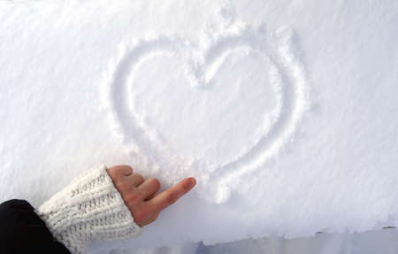 Photo pour Hand draws a sign of the heart on the snow. - image libre de droit