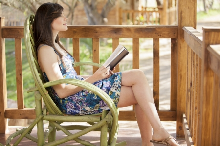 Gorgeous young woman sitting on a log cabin s deck and reading a book