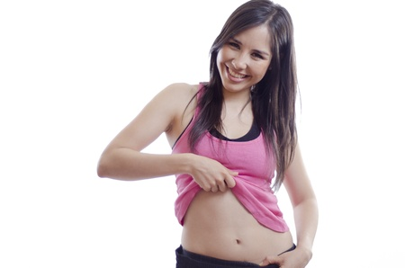 Young beautiful woman lifting her shirt to show her belly