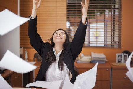 Happy businesswoman tossing papers in the air, excited about something