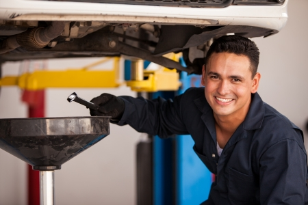 Happy young mechanic draining engine oil at an auto shop for an oil change