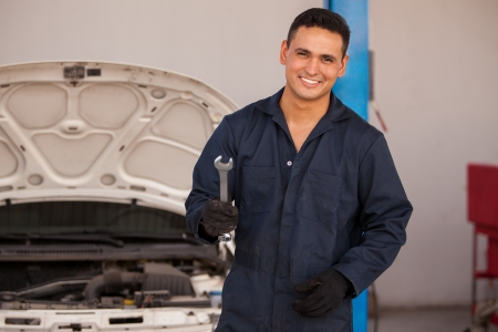 Handsome young mechanic wearing an overall and smiling while holding a wrench