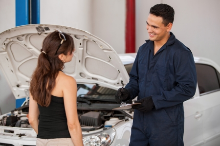 Handsome young mechanic receiving a car at an auto shop from a female customer and smiling