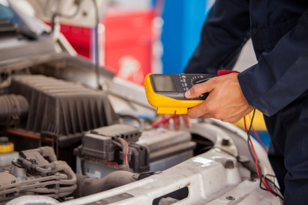 Closeup of a mechanic checking a car battery at an auto shop