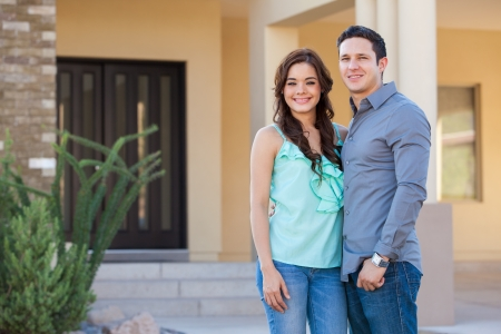 Happy young Latin couple in front of their new house