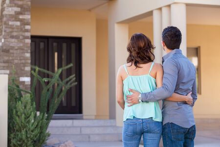 Cute young couple holding each other and looking at their new house