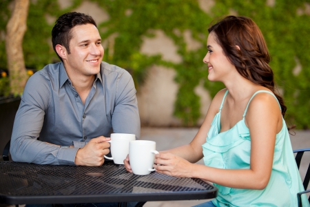 Good looking Latin couple drinking coffee and smiling on their first date at a restaurant