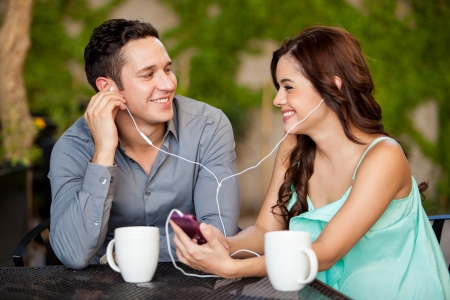 Photo pour Happy Hispanic couple listening to some music while having coffee on a date - image libre de droit