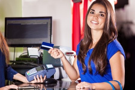 Beautiful Hispanic woman paying with a credit card at a clothing store