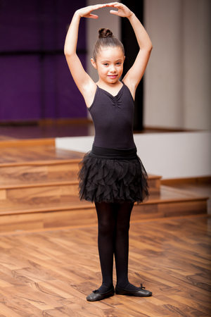Beautiful little ballerina wearing tights and a skirt practicing a ballet pose in dance class