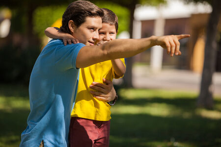Young Latin father pointing and showing something to his cute son outdoorsの写真素材