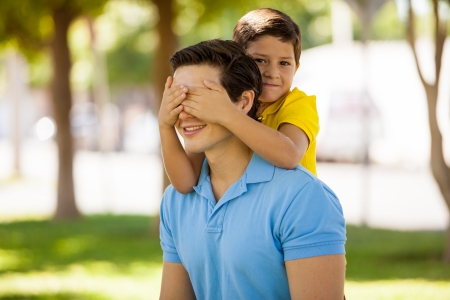 Cute little boy covering his dad s eyes for fun while spending the day outdoors