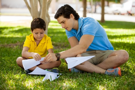 Young father teaching his son how to fold paper planes while spending time together in a park