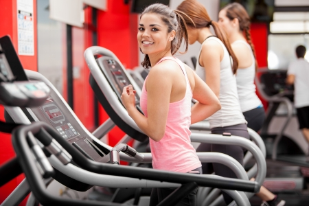 Pretty girl working out in a treadmill at the gym and smiling