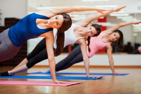Beautiful group of women practicing the side plank yoga pose during a class in a gym